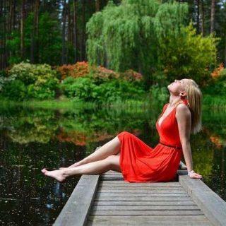 Žena v červených šatek na břehu rybníka